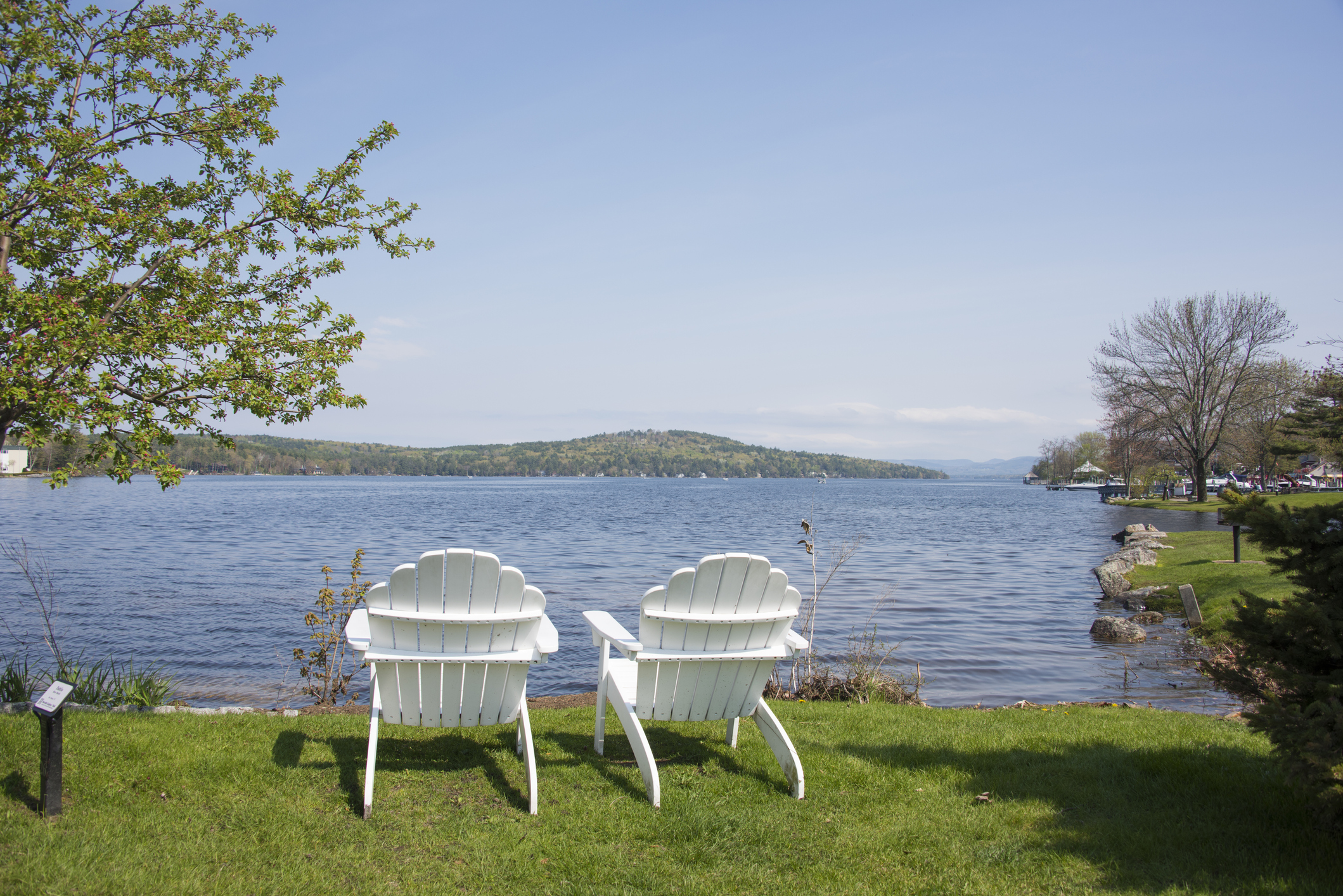 Two white wooden chairs with views of lake