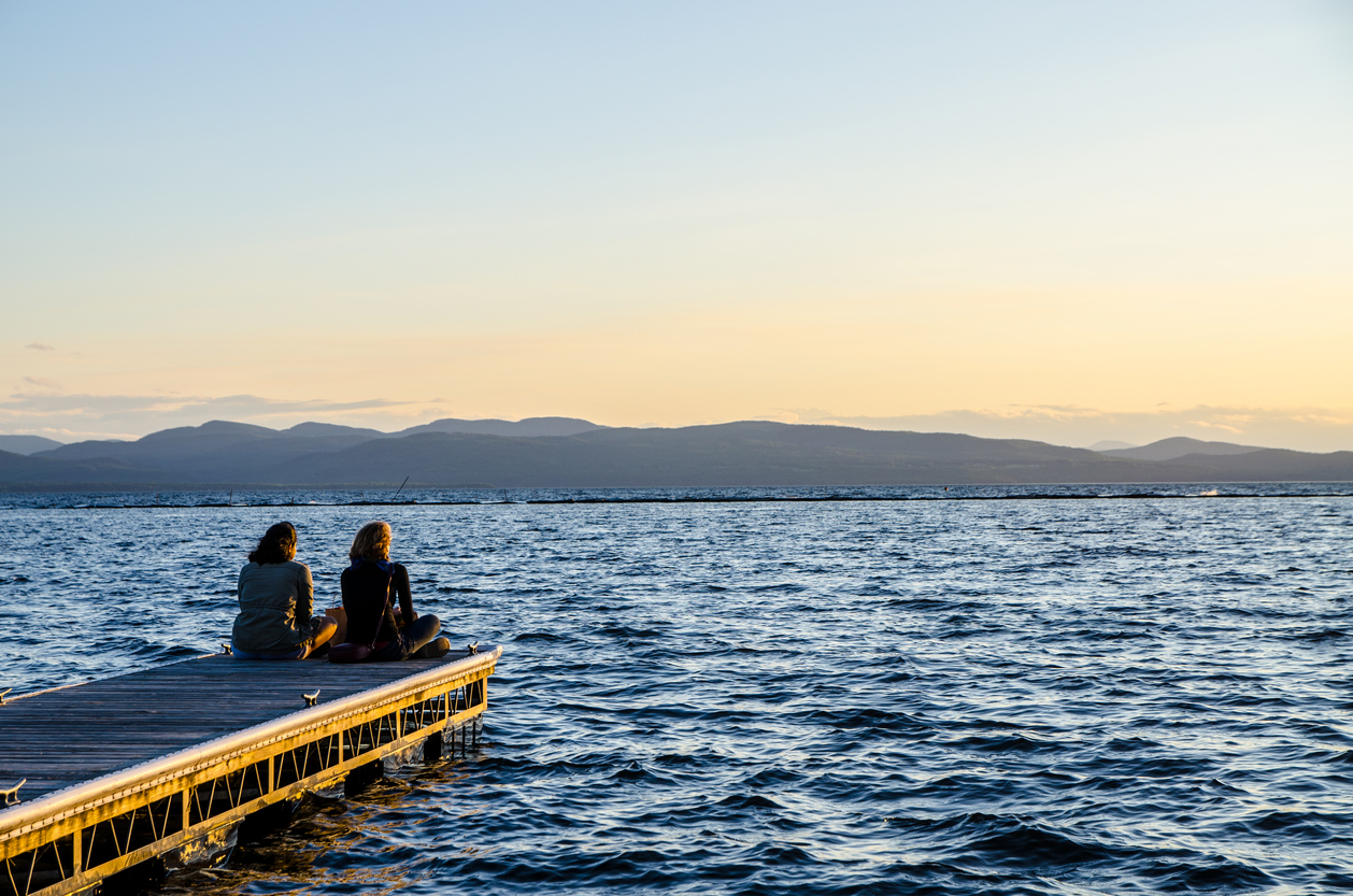 People sitting at the end of dock during sunset