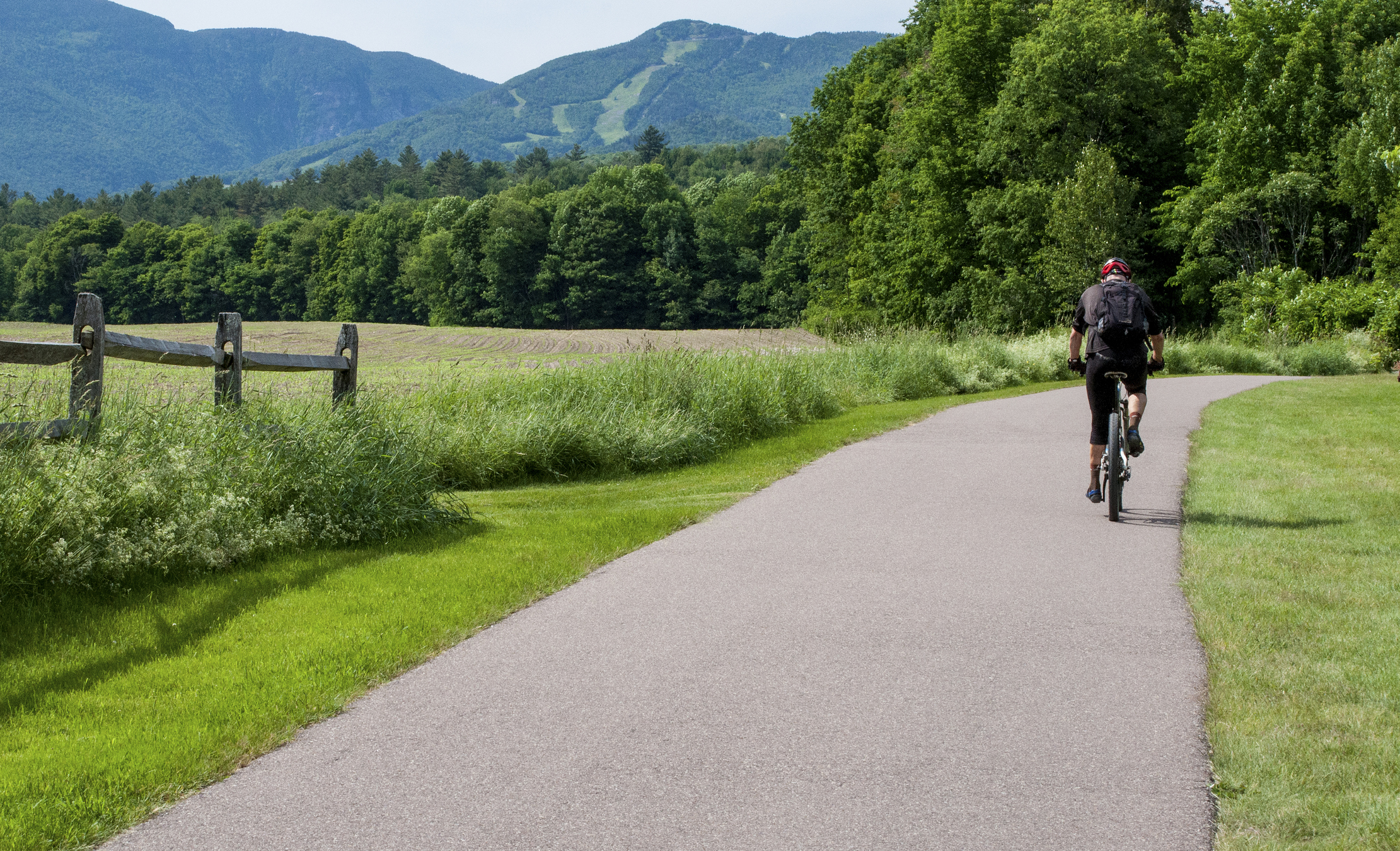 A bicycle rider pedals over the Recreation Path in