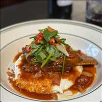 Charred tomato with braised short rib over creamy polenta, get it at Antique Bar and Bakery!