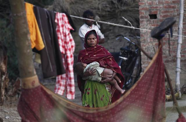 A woman holds her child as she stands outside her house at Dalit village of Bhaddi Kheda