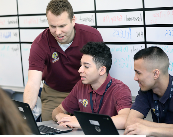 Teacher and two boys in front of laptops