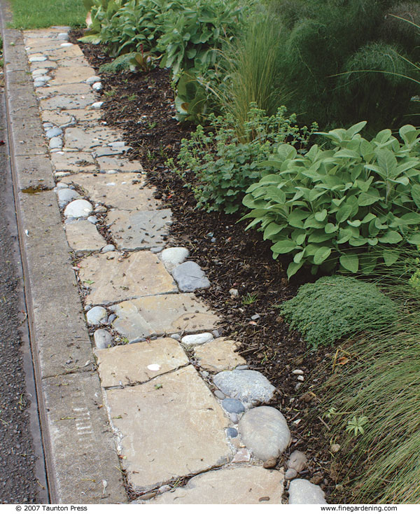 Pebbles Fill The Spaces Between Large Flat Stones In This Edging Along A  Streetside Curb.