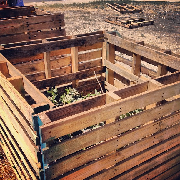 composting pile with wooden barrier around it