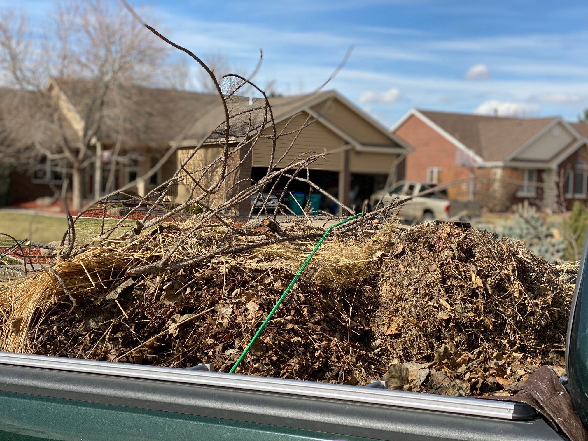 compost bin with brown material and stick