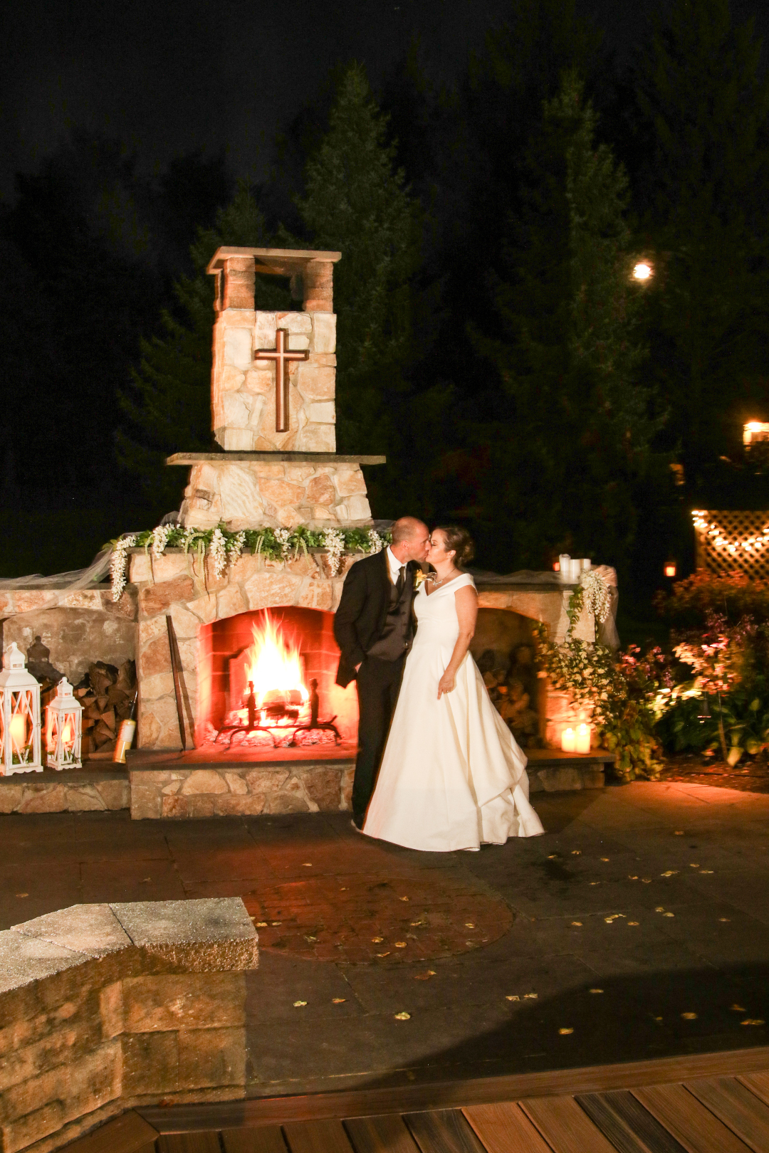 A newly married couple kiss in front of an outdoor fireplace