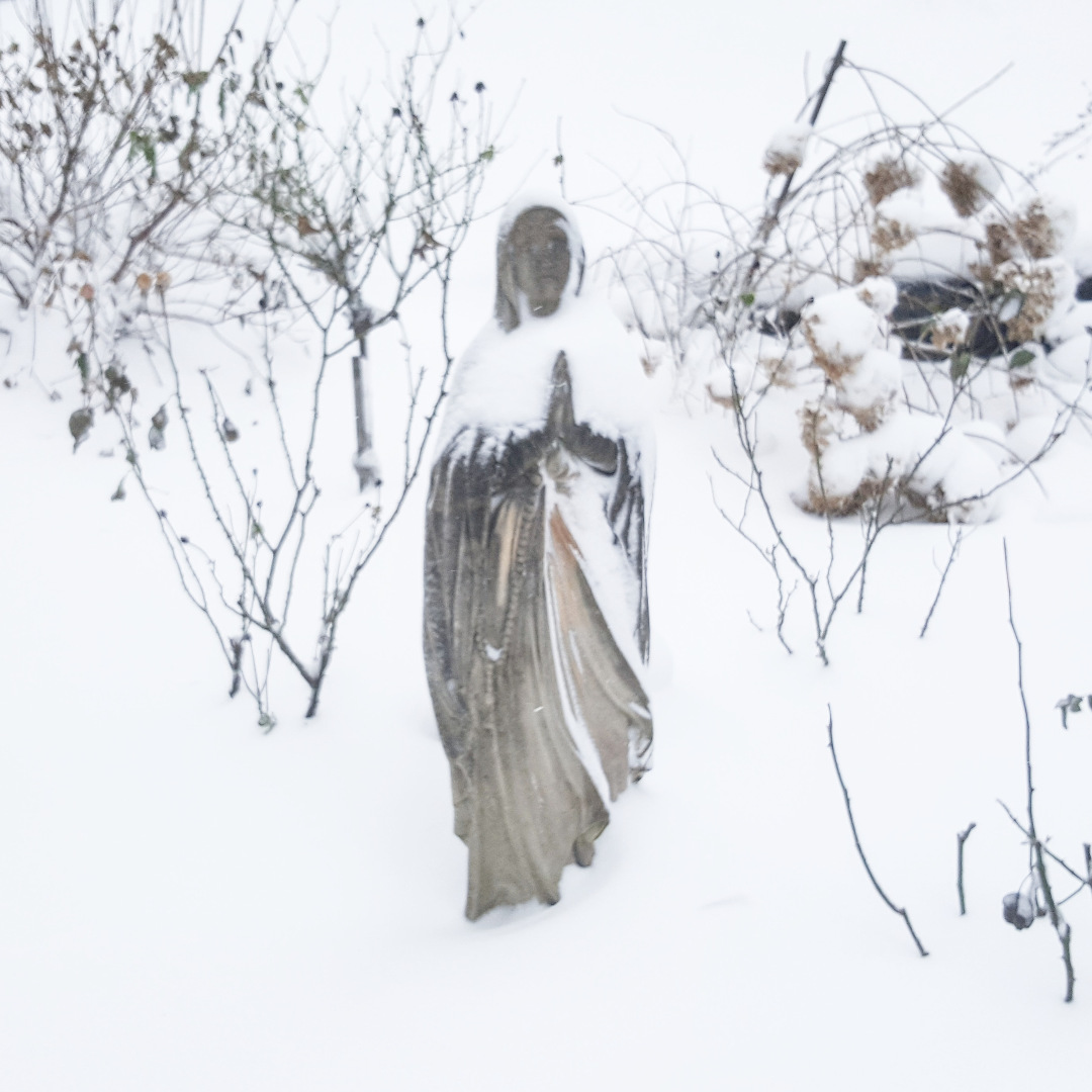 A statue in a snowy garden