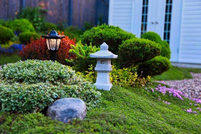 small garden sculpture next to bushes