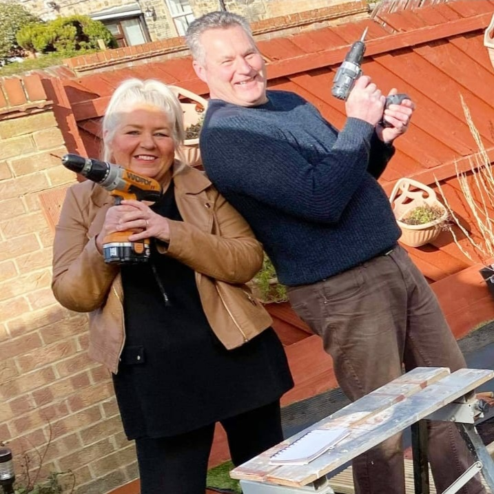 A couple holding electric drills