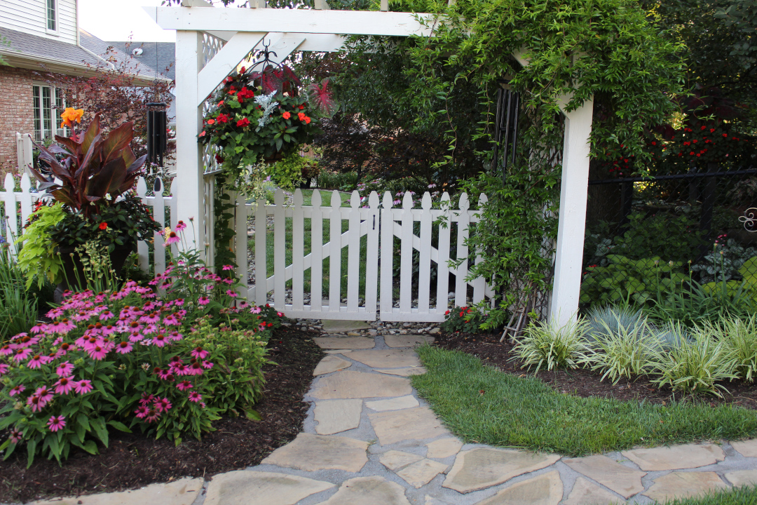 large garden gate surrounded by flowers