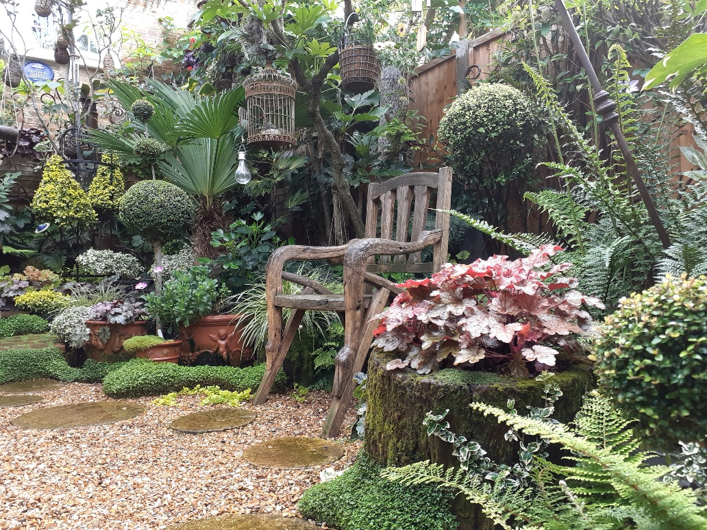 wooden garden chair surrounded by lush plants