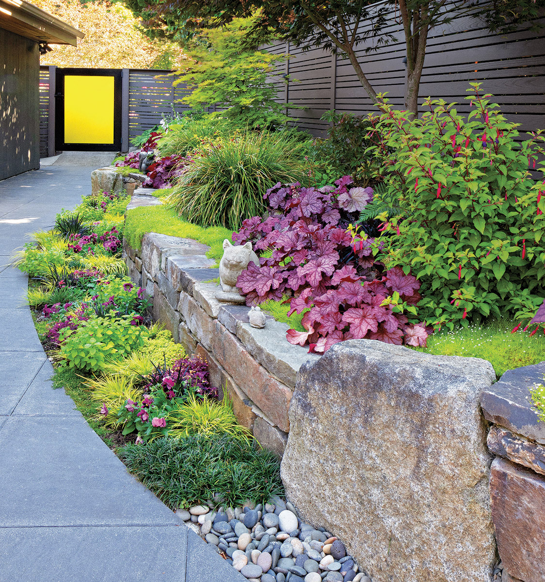Chartreuse can unite a planting by being the main theme of the area. Picking up on the yellow of the door, the chartreuse plants here create a vibrancy to the bed that the area needs, given the dark and gray hardscape. Using the yellow of the door throughout the bed would have been garish, requiring sunglasses of anyone attempting to view it. The numerous pops of purple provide a counterpoint to the chartreuse and a connection to the house and the fence.