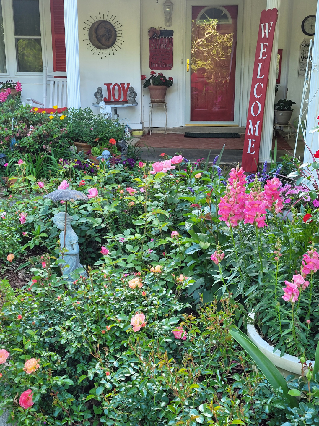 Front porch with a garden full of pink flowers