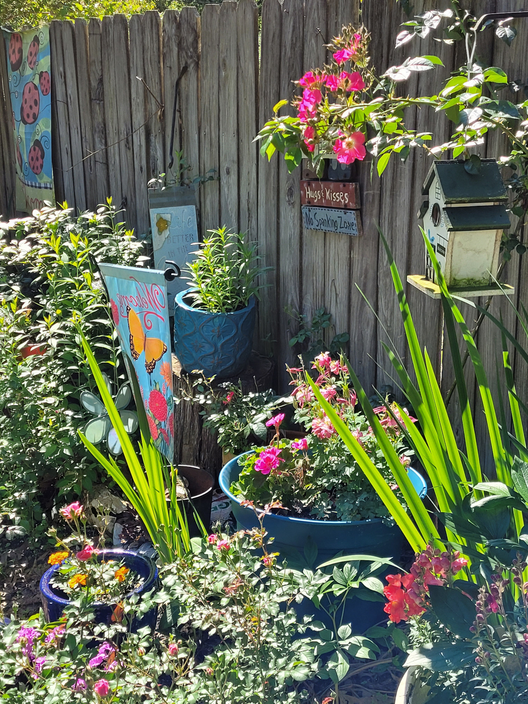 A wooden fence with many flowers in pots in front of it