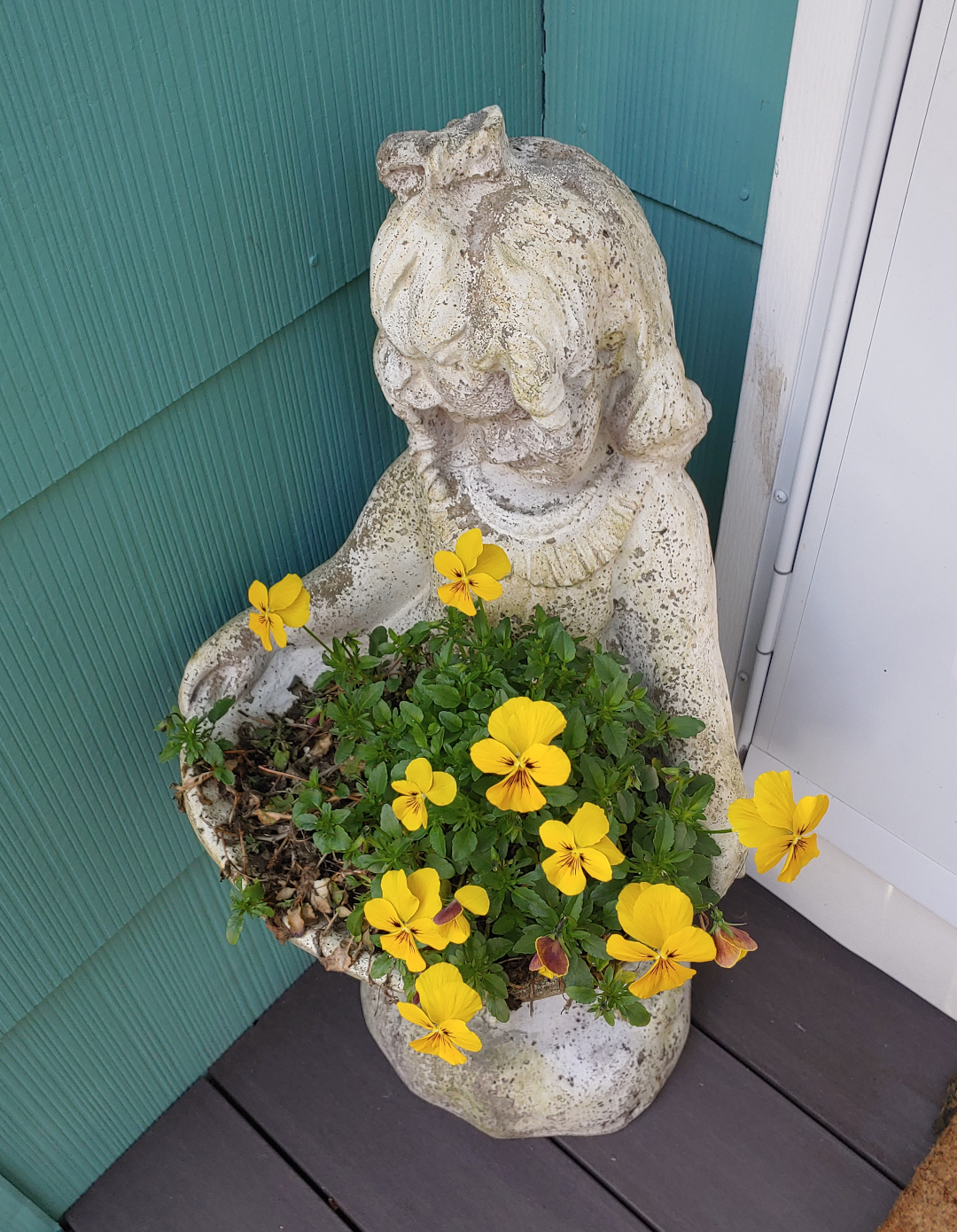 Planter in the shape of a girl holding a basket with yellow flowers growing in it