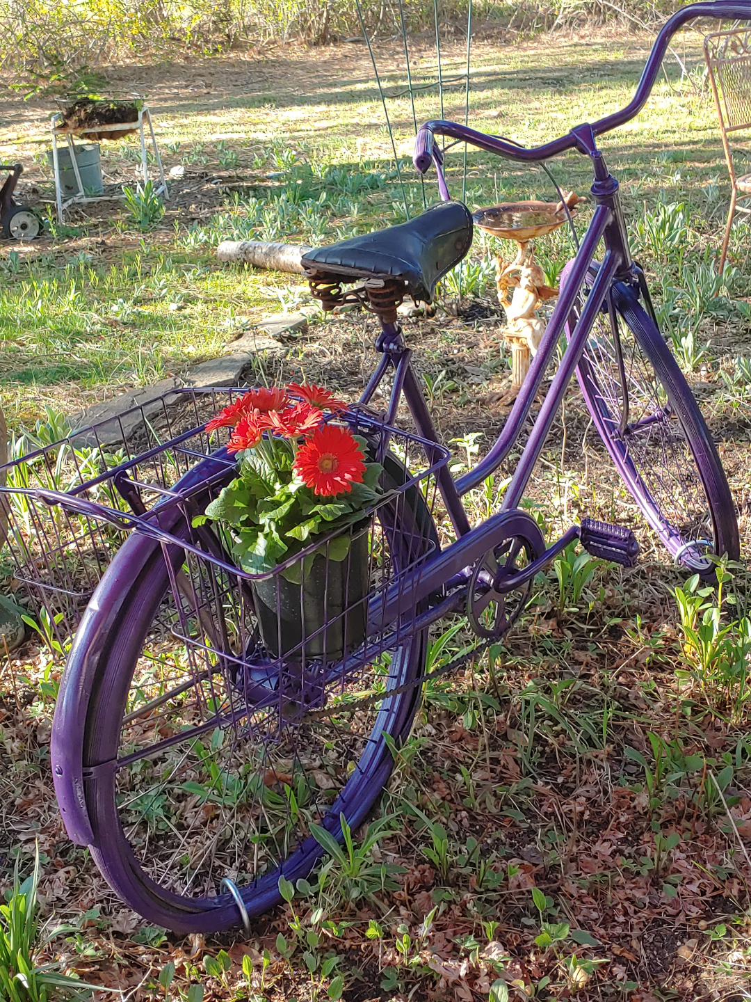 A bicycle painted purple with red daisies in the basket
