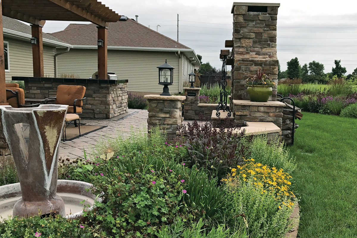 From furniture to hardscaping, one hue repeats throughout the design of the patio. The stonework around the fireplace, the fountain accents, and the rich sepia in the wood of the pergola highlight the burgundy foliage and seed heads of 'Dark Towers' penstemon and underscore it as the star of the patio garden.
