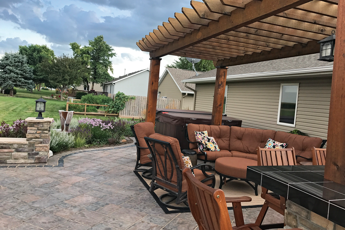 Thematic color integrates the patio as a transition to the garden. From the lighter cinnamon-orange color of the chair cushions to the dark maroon of the hot-tub cover, shades of brown, red, and purple blend seamlessly with foliage of 'Dark Towers' penstemon in the patio garden beyond.