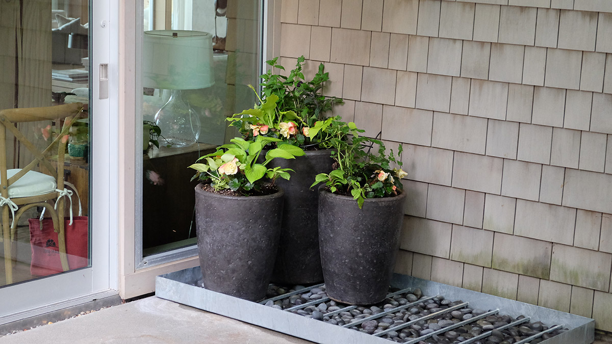 three shade containers on a porch with perennials