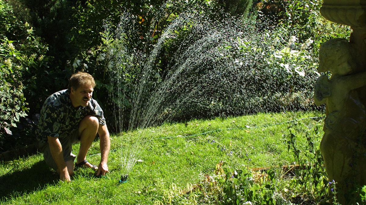 man adjusting a sprinkler