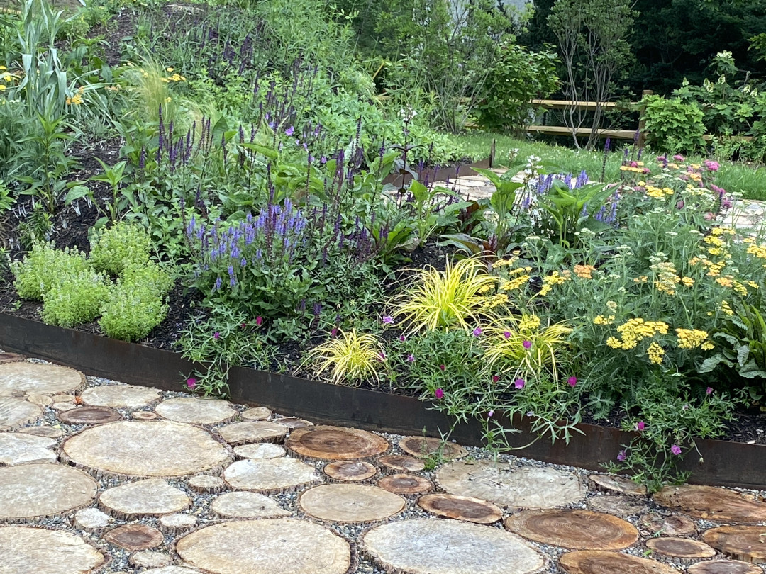 A mounded garden full of flowers and colorful foliage