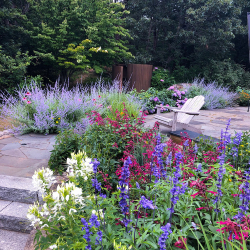 A stone patio with a chair surrounded by purple, blue, burgundy and white flowers