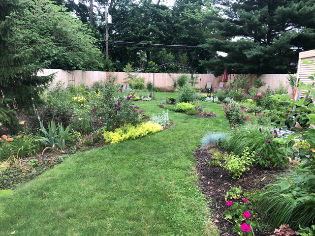 backyard with lots of garden beds and tan fence