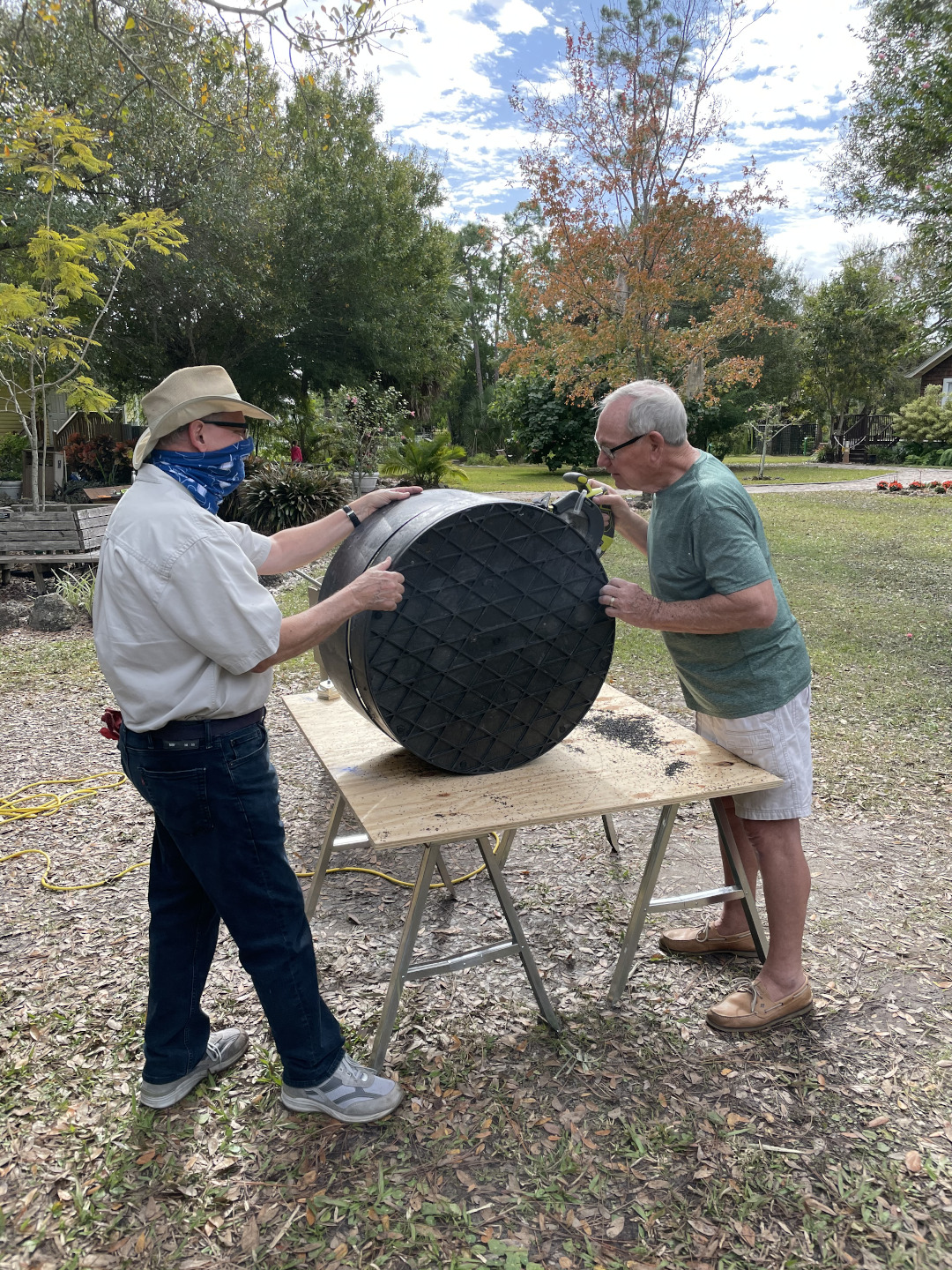 Two men slicing a plastic barrel into rings