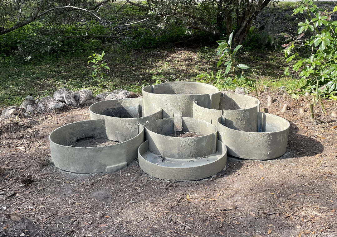 Rings set in the ground covered with sand and painted to resemble stone