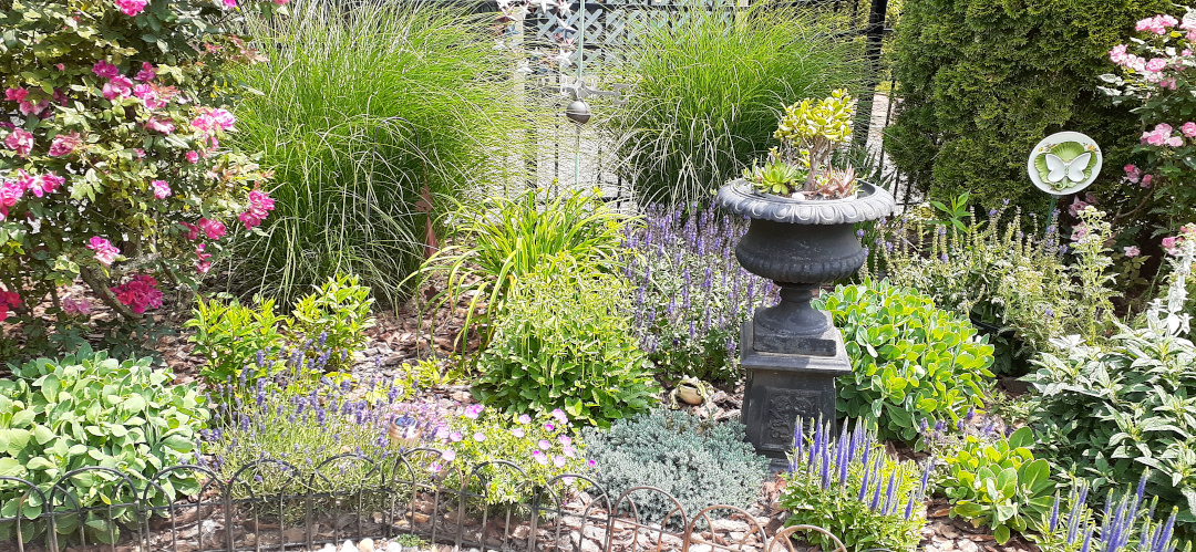 garden bed with a tall urn in the center of it