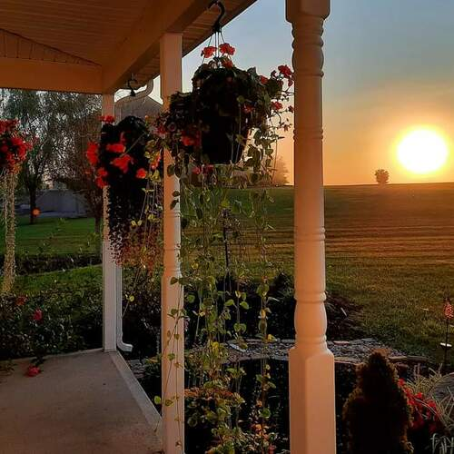 covered porch with hanging baskets overlooking a sunset