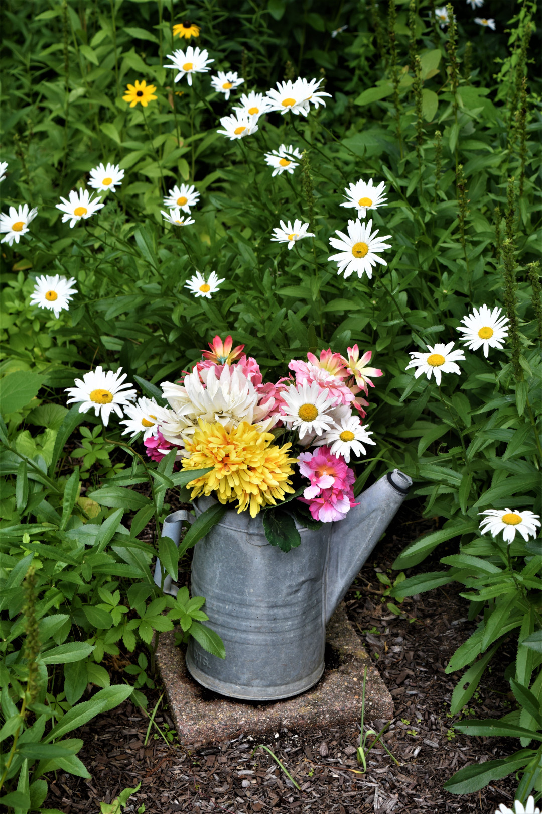 old watering as a flower vase in the garden