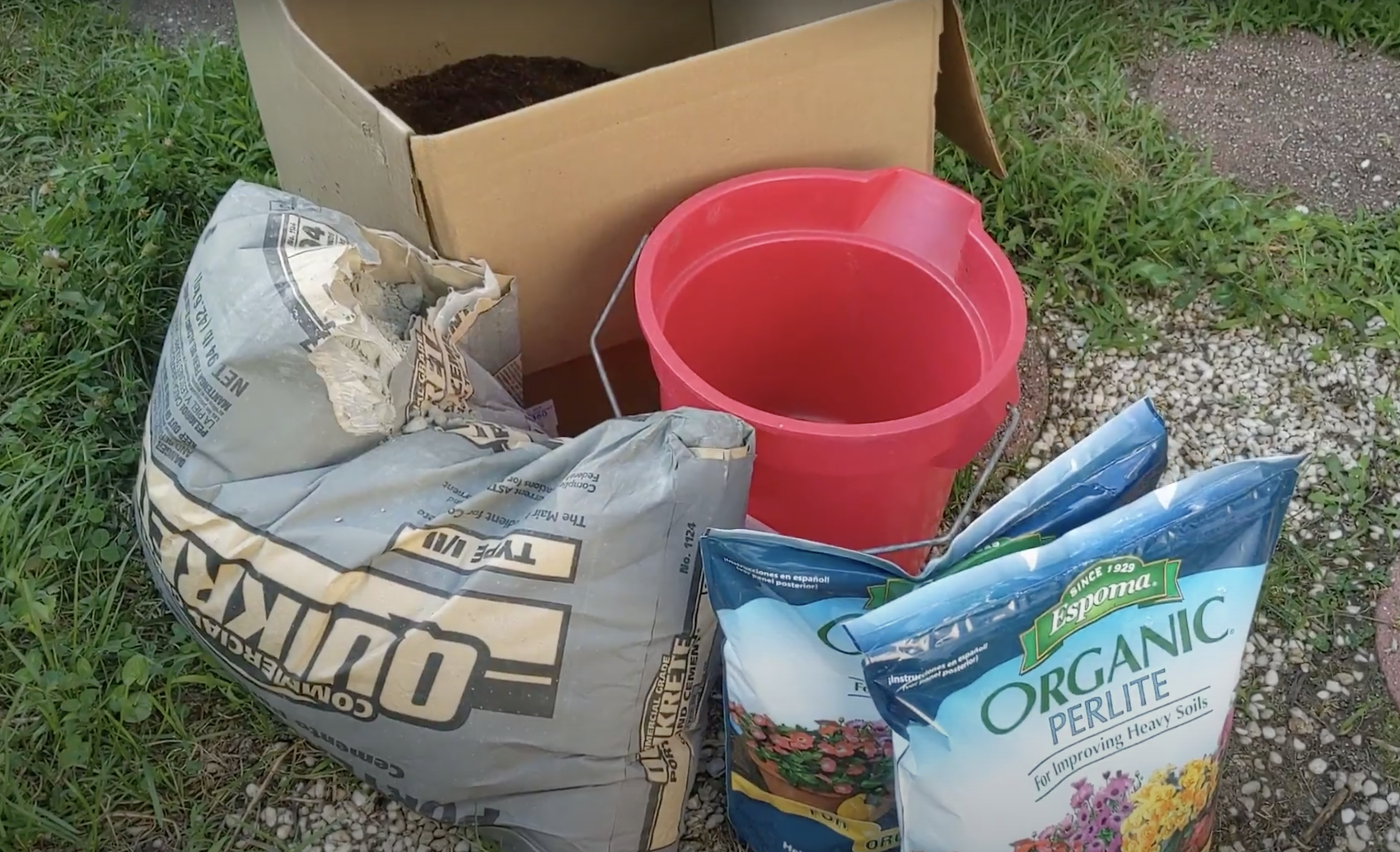 perlite, bag of portland cement, bucket, and coconut coir in a cardboard box