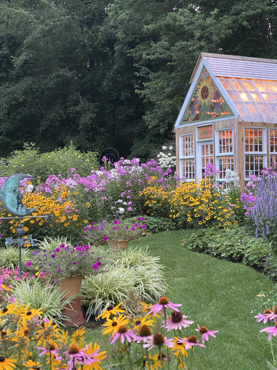 big summer plants in bloom leading to greenhouse