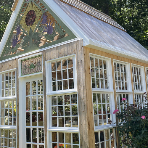 greenhouse with sunflower design on front gable