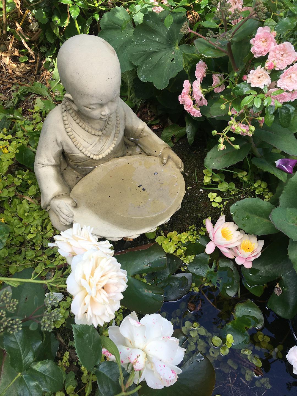 A garden statue is hidden in the lush garden.