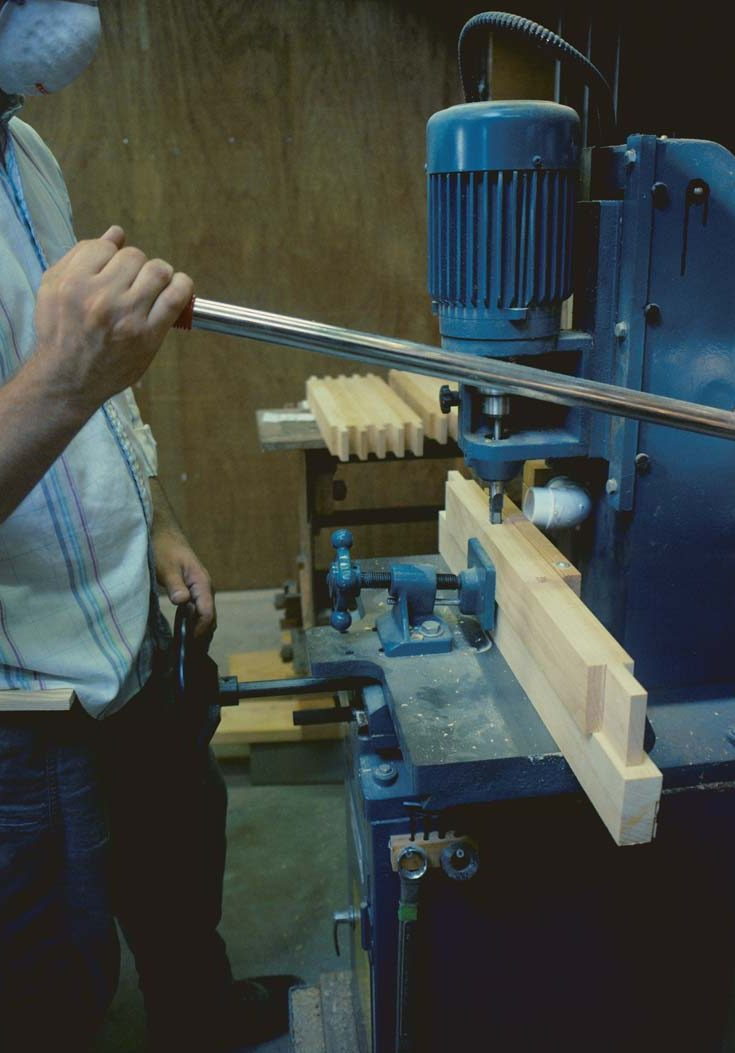 Cutting mortises. The author used a hollow-chisel mortiser to cut mortises in the four cross muntins. To reduce tearout, the mortises were cut in stock that was later ripped into three muntins.