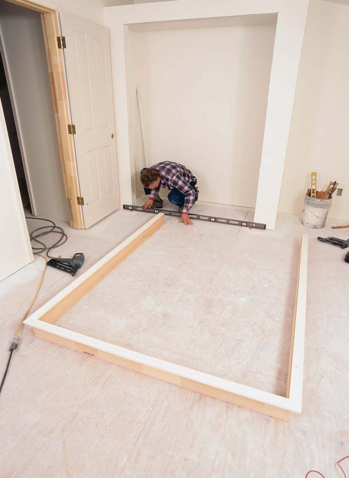 Shims elevate the jambs. With a spirit level long enough to span the rough opening, the author assesses the floor for level and places shims accordingly next to the trimmer studs.