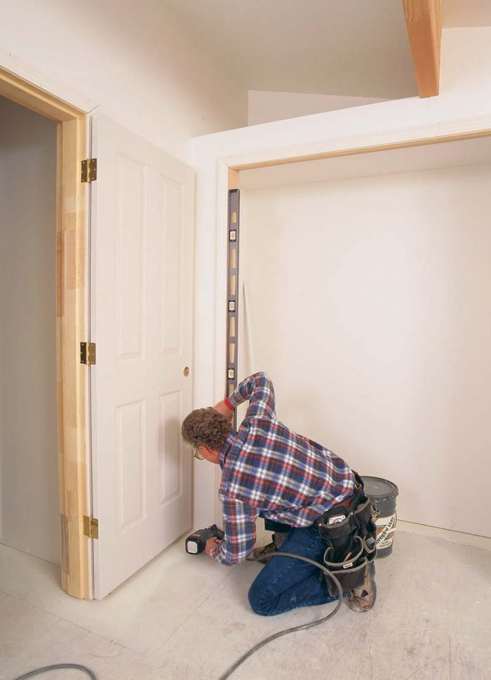 Plumb the side jamb. Britton uses the 6-ft. level to check the side jamb for plumb, moving the bottom of the jamb toward or away from the trimmer until the bubble is centered.