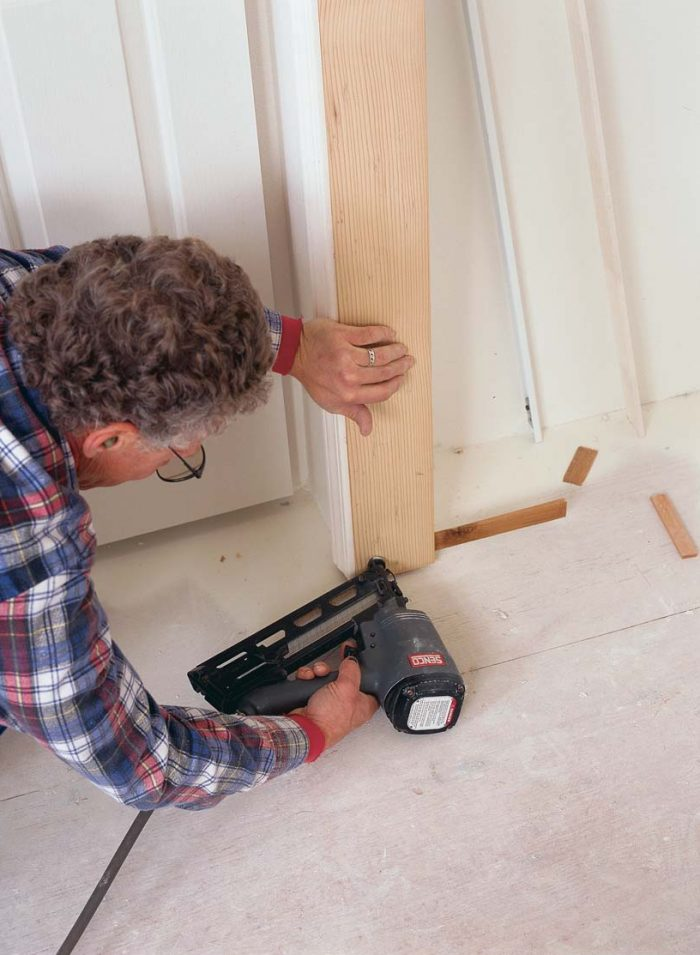 Shim the jamb, and nail it home. Once the jamb has been plumbed, it can be permanently affixed to the trimmer.