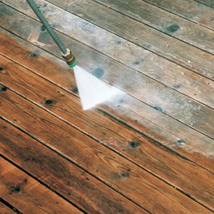 Be careful with the pressure washer. For maximum cleaning with minimal abrasion, the author holds the 15° spray tip 6 in. to 9 in. above the deck and gradually sweeps across the boards in a flattened pendulum motion.