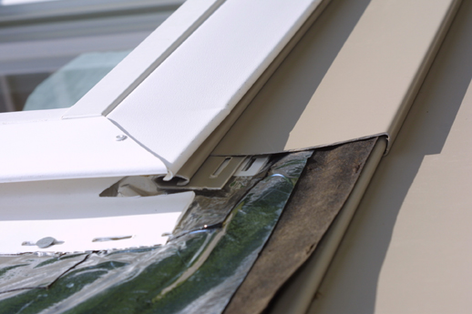 Behind the window casing, undersill trimsecures the cut vinyl panel under a win-dow. T