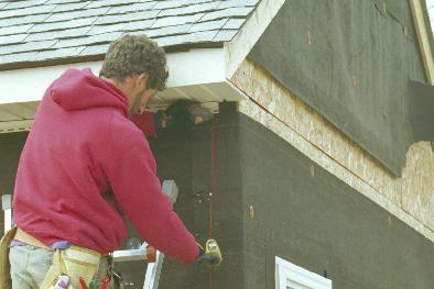 Man on ladder use chalklines to keep corner boards straight