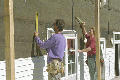 Man measures panels with measuring tape