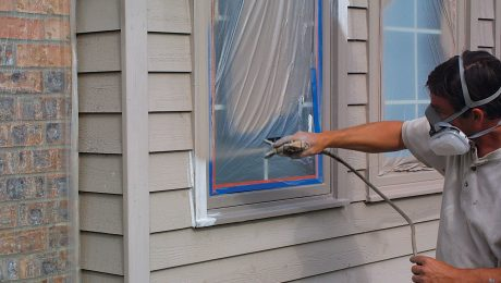 A person spraying paint around a taped window