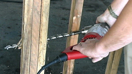 person drilling a hole thru studs