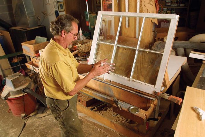 With the sash propped up on a homemade easel, he works glazing compound into a 3⁄8-in.-diarope before pressing it into place.
