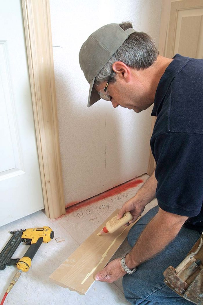 Use 11⁄2-in. finish nails to attach trim pieces because longer nails can extend into the door. Carpenter's glue backs up the baseboard's fasteners.