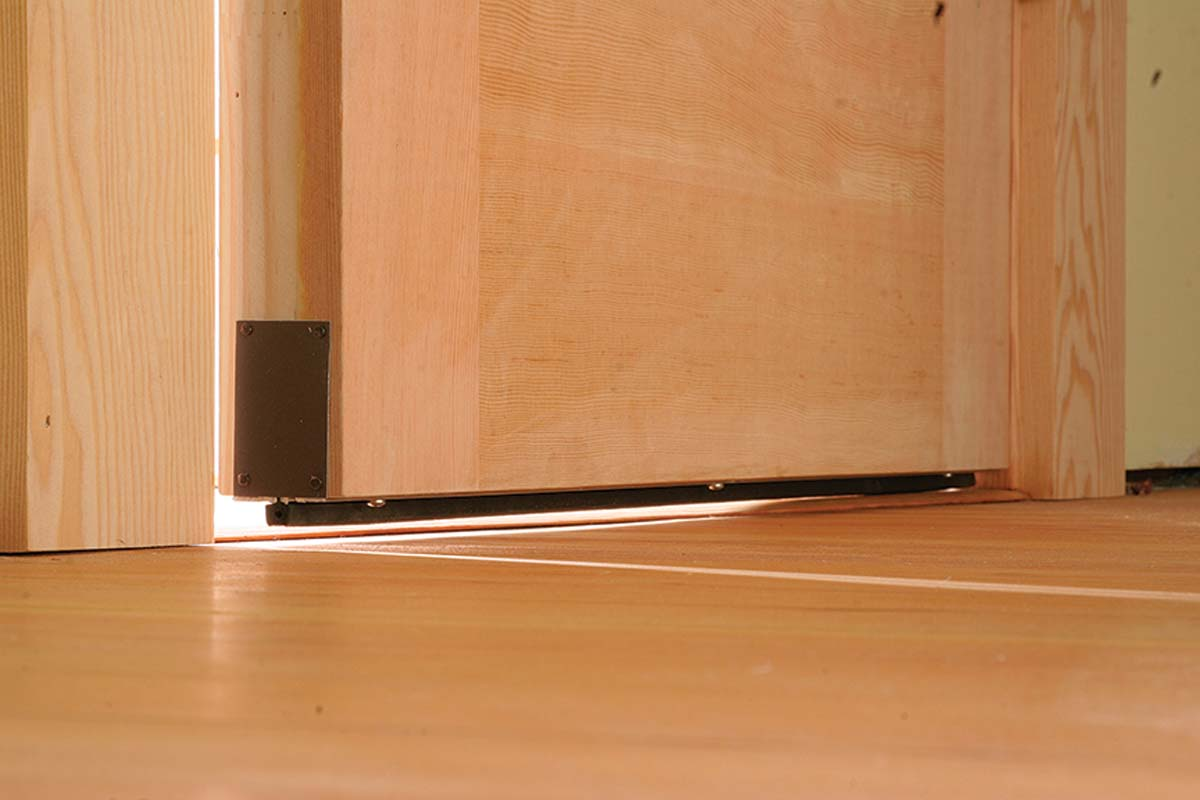 When the door closes, a spring-loaded pin compresses against the hinge-side door jamb to drop the seal.