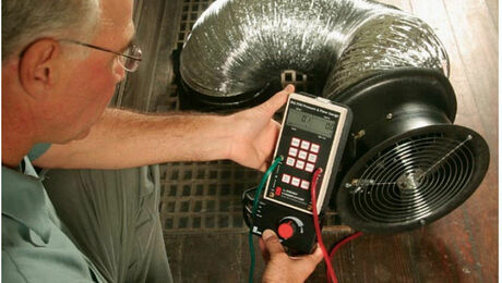Photo of man performing duct blaster test on HVAC system